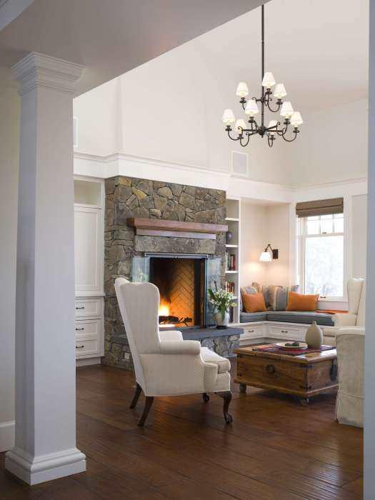 Гостиная с каменным камином и угловым диваном на подоконнике