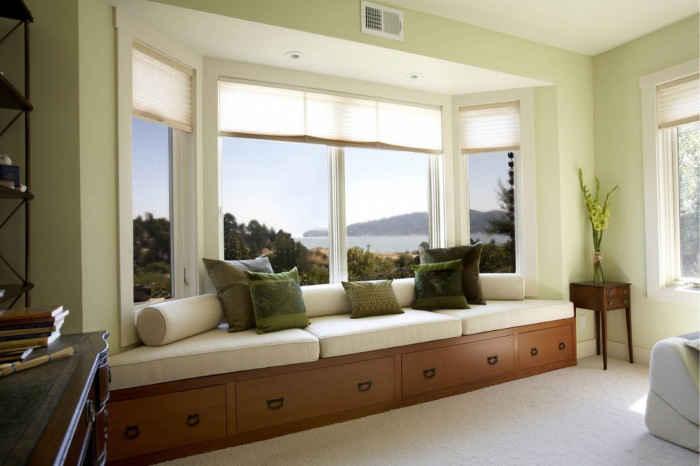 Элегантный белый диван на подоконнике с подушками зеленого цвета